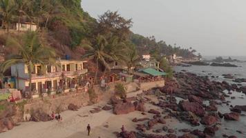Exotic Guesthouses near rocky shoreline in Arambol Beach in North Goa, India - Aerial dronie fly away wide shot video