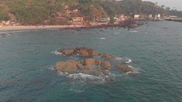 ondas batendo suavemente nas rochas do mar, praia de arambol, goa, índia. vista aérea