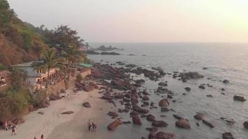 Rocky ocean coast and old buildings in Arambol Beach at sunset in Goa, India - Aerial Fly-over shot video