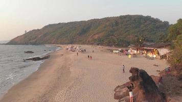 la gente pasea por la playa de Arambol, las tranquilas aguas del océano. goa, india. Antena aérea video
