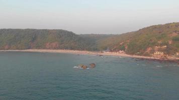 Mar Arábigo lavando en la costa de Arambol en Goa, India - Toma aérea amplia sobrevuelo video