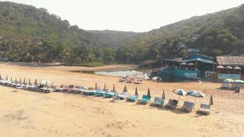 Beach chairs and shoreline shacks in Arambol Beach in North Goa, India video