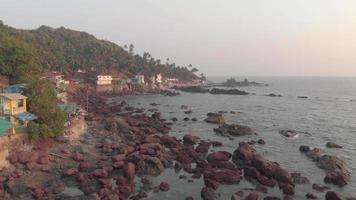 voe sobre as rochas na praia de arambol, goa, índia. pequenas ondas suaves