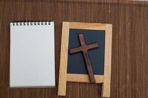 Flat lay of a notebook with a chalkboard sign and cross