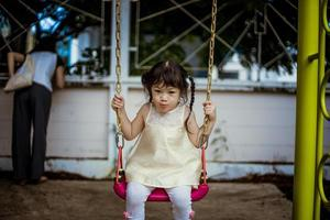 Young girl swinging in a park photo