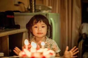 niña preparándose para soplar velas de cumpleaños