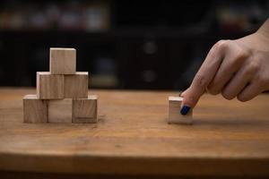 Person stacking wooden blocks photo