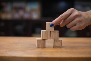 Hand stacking wooden blocks photo