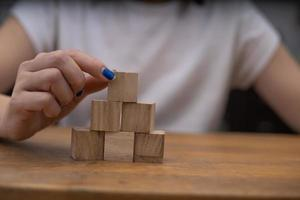 Person carefully stacking wooden blocks photo