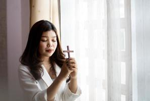 Woman holding a cross in prayer photo
