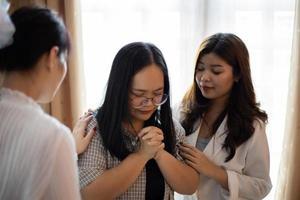 Three women in prayer photo