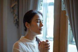 mujer rezando cerca de una ventana