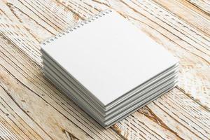 Cuadernos en blanco sobre fondo de madera foto