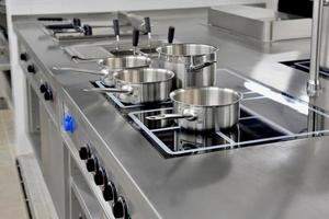 Stainless steel pots built on the stove in the restaurant kitchen photo