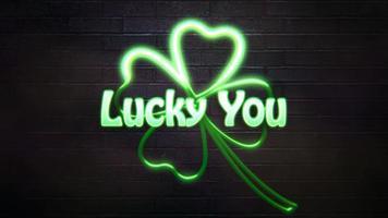 Animation Nahaufnahme Glück Sie Text und Bewegung neongrüne Kleeblätter auf Saint Patrick Day glänzenden Hintergrund video