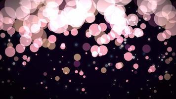 movimento e voar partículas rosa e bokeh redondo em fundo escuro video