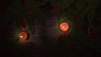 geanimeerde close-up kerst kaars en groene boomtakken op hout achtergrond video
