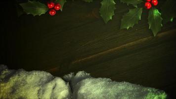 geanimeerde close-up witte sneeuw en groene kersttak op hout achtergrond video