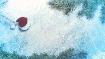 geanimeerde close-up kerstmuts en groene boomtakken op glanzend ijs achtergrond