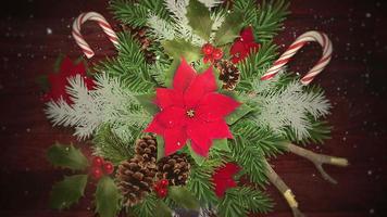 Flocons de neige blancs gros plan animé sur des bonbons et des branches de Noël vertes, fond de bois video