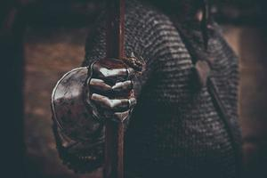 Knight's hand in metal gloves holding spear