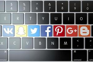 2018-- Illustrative editorial of various social networks and services icons over computer keyboard