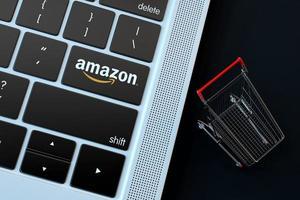2018: editorial ilustrativa del logotipo de Amazon sobre el teclado de la computadora con carrito de compras