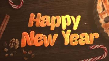 geanimeerde tekst van het close-up gelukkig nieuwjaar, snoep en kersttaart op houten achtergrond video