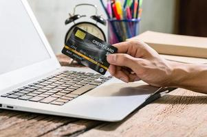 People use credit cards to shop online through notebook computers photo