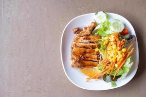 Filete de pollo a la plancha con salsa teriyaki sobre un fondo marrón