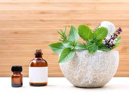 Mortar with fresh herbs and essential oil photo