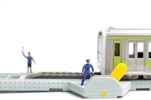 Miniature railway staff working at s railway on a white background photo