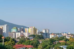 Vista horizontal de edificios y follaje sobre un fondo de cielo azul foto