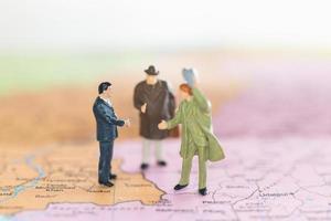 Turistas en miniatura apretón de manos sobre un fondo de mapa del mundo, el viaje y el concepto de viaje foto