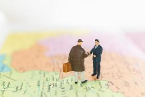 Miniature tourists handshaking on a world map background, journey and travel concept