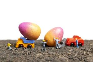 Miniature people working on Easter Eggs for Easter day with a white background photo