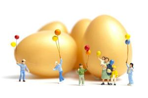 Miniature people holding balloons celebrating Easter on a white background