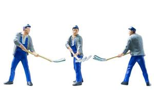 Miniature construction workers concept isolated on a white background photo