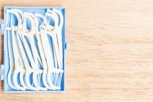 Hilo dental para dispositivos bucales sobre un fondo de madera