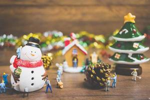Gente en miniatura creando adornos navideños sobre un fondo de madera foto