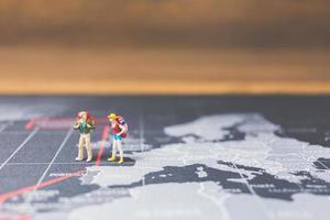 Mochileros en miniatura caminando sobre un mapa del mundo, concepto de turismo y viajes