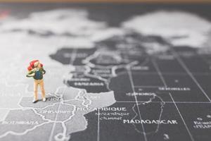 Mochilero en miniatura caminando sobre un mapa del mundo, el turismo y el concepto de viaje