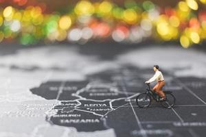 Miniature traveler riding a bicycle on a world map, traveling and exploring the world concept