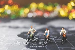 Miniature travelers riding a bicycle on a world map, traveling and exploring the world concept photo