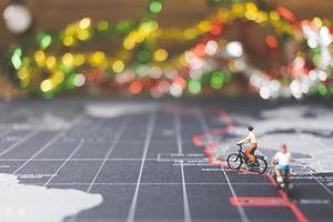 viajeros en miniatura montando una bicicleta en un mapa del mundo, viajando y explorando el concepto del mundo