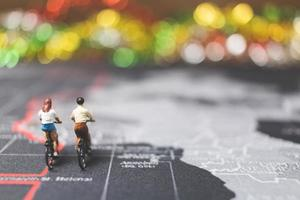 Miniature travelers riding a bicycle on a world map, traveling and exploring the world concept
