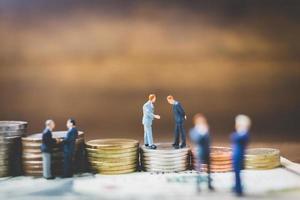 Empresarios en miniatura en dinero sobre un fondo de madera foto