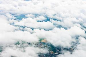Top view from an airplane showing white clouds and the Earth below photo