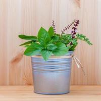 Bucket of herbs on wood photo