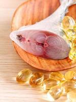 Pastillas de pescado y aceite de pescado en madera foto